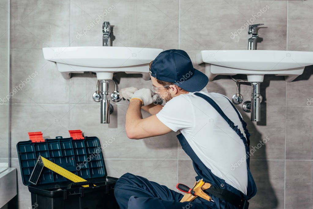 back view of young professional plumber fixing sink in bathroom