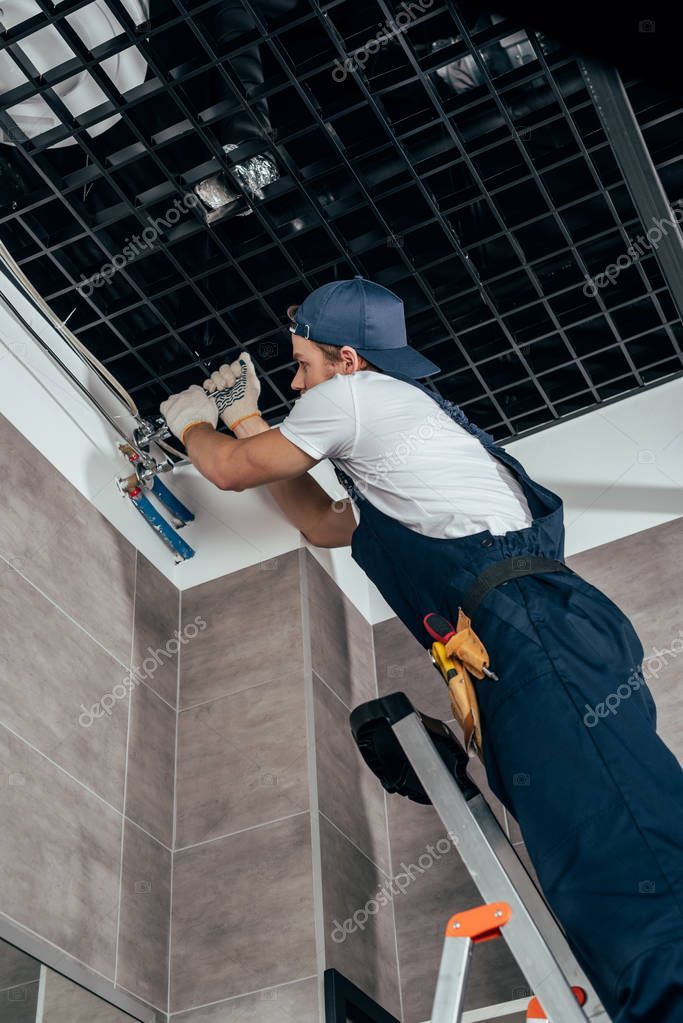 low angle view of plumber working with pipes in bathroom