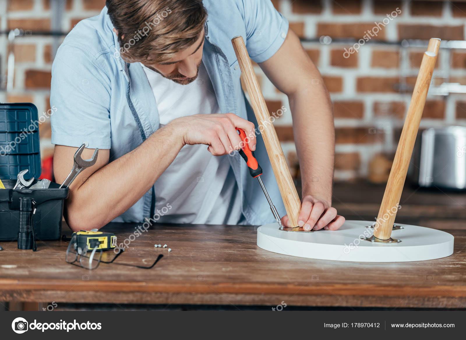 Ritagliata colpo giovane bello riparazione sgabello con cacciavite