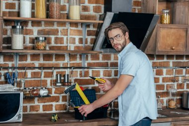 young man in eyeglases taking tools from toolbox and looking at camera in kitchen