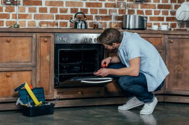 casual young man holding screwdriver while repairing oven in kitchen