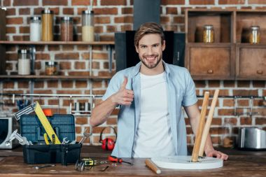 handsome young man smiling at camera and showing thumb up while repairing chair at home