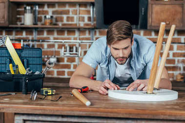 concentrated young man repairing stool with tools at home