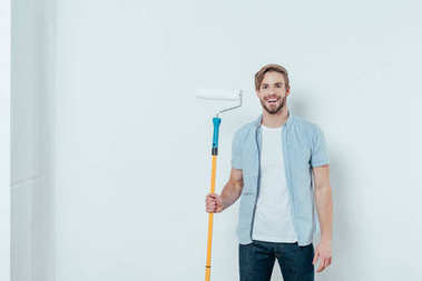 handsome young man holding paint roller and smiling at camera on grey