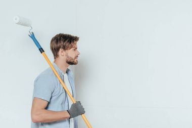 side view of young man holding paint roller and looking away on grey