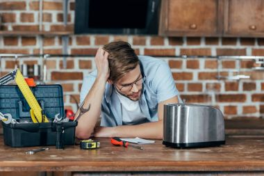 frustrated young man in eyeglasses looking at broken toaster at home