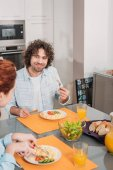Photo happy couple eating in kitchen at home