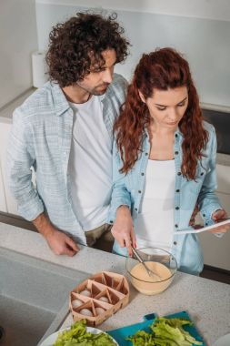 high angle view of girlfriend preparing batter with recipe on tablet