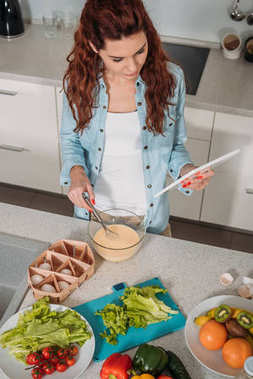 high angle view of girl preparing batter with recipe on tablet