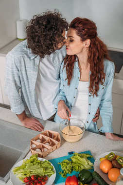 high angle view of heterosexual couple kissing at kitchen