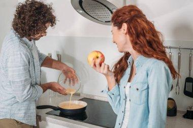 boyfriend pouring batter on frying pan