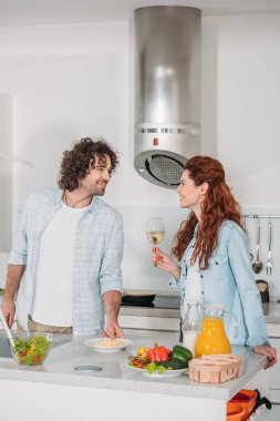 happy couple looking at each other in kitchen