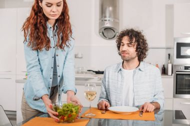 girlfriend putting salad on table in kitchen