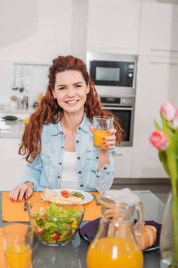 smiling girl sitting at table with meal and holding glass of orange juice