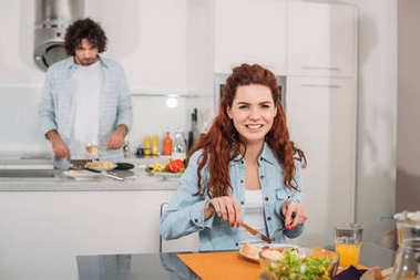 smiling girlfriend eating while boyfriend cooking at kitchen
