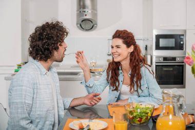 smiling girlfriend feeding boyfriend in kitchen