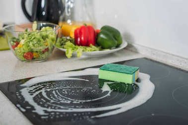cleaning sponge and soap on kitchen stove