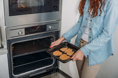 cropped image of woman taking homemade biscuits from oven