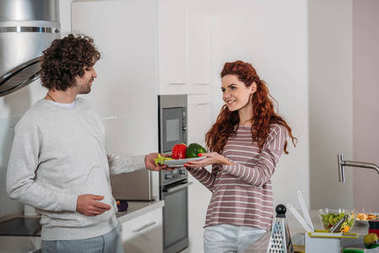 girlfriend giving boyfriend plate with vegetables