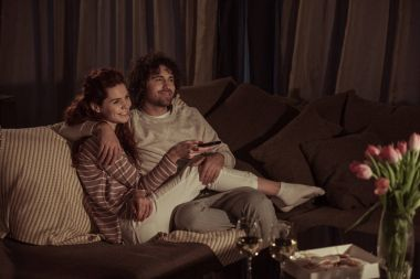 happy couple watching tv on sofa in evening