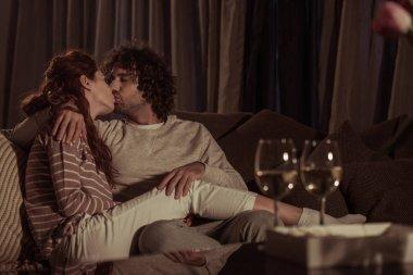 heterosexual couple kissing on sofa in evening