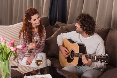 handsome boyfriend playing song with guitar to girlfriend at home