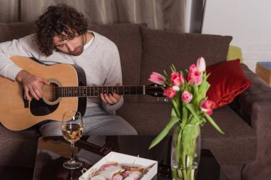 handsome man playing guitar at home