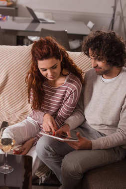 smiling couple using tablet while sitting on sofa at home
