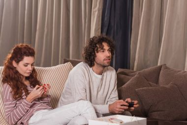 Girlfriend waiting while boyfriend playing video game stock vector