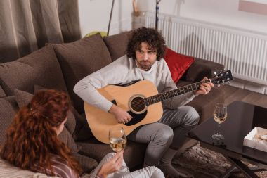 handsome boyfriend playing song with guitar to girlfriend