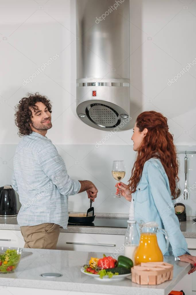 boyfriend cooking and girlfriend drinking wine