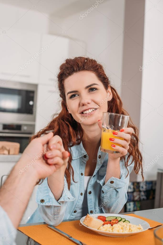 cropped image of smiling couple holding hands at table in kitchen