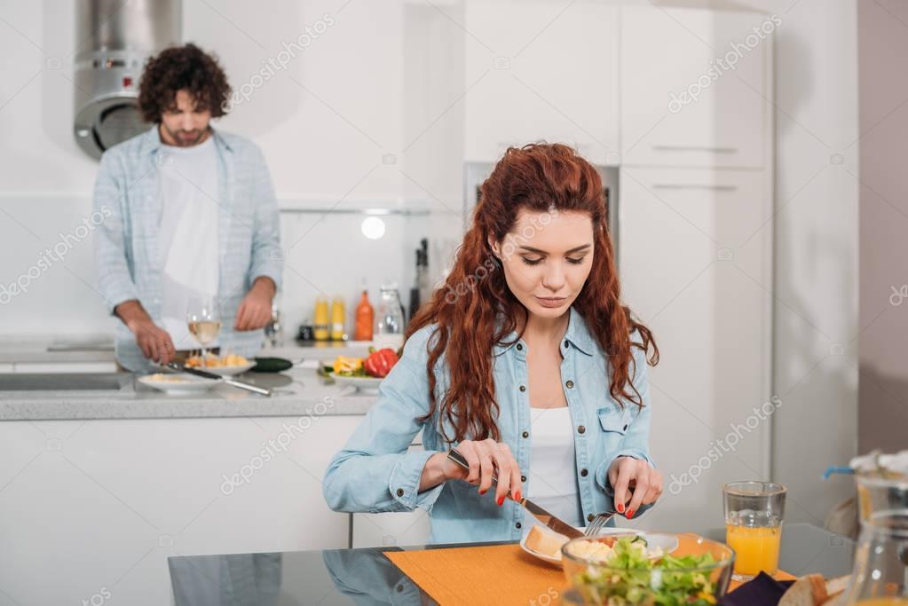 girlfriend eating while boyfriend cooking at kitchen
