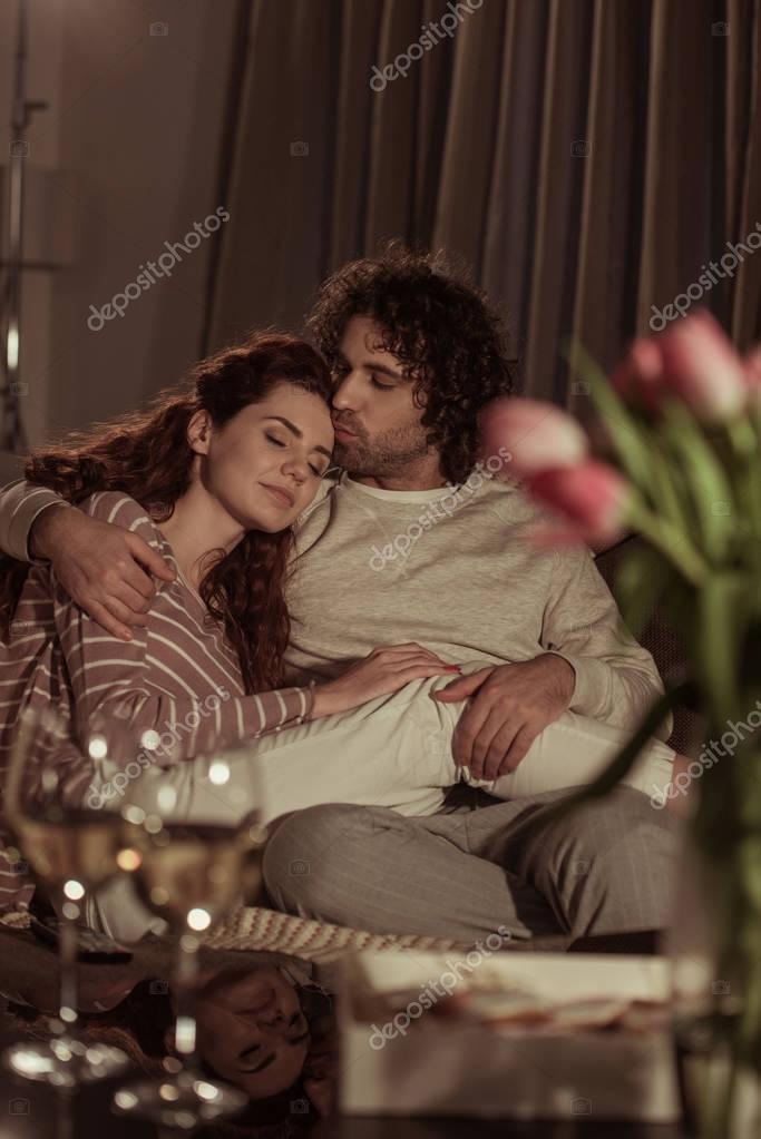 boyfriend kissing sleeping girlfriend on sofa