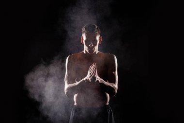 shirtless young sportsman applying talcum powder on hands on black