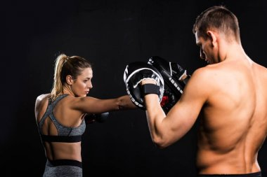 shirtless male trainer training with female boxer isolated on black