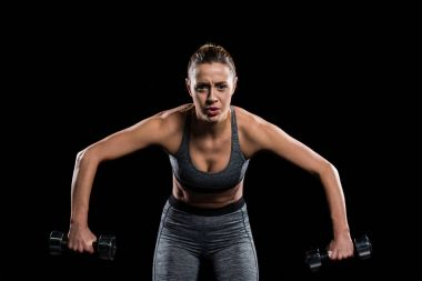 tired sporty young woman exercising with dumbbells and looking at camera isolated on black