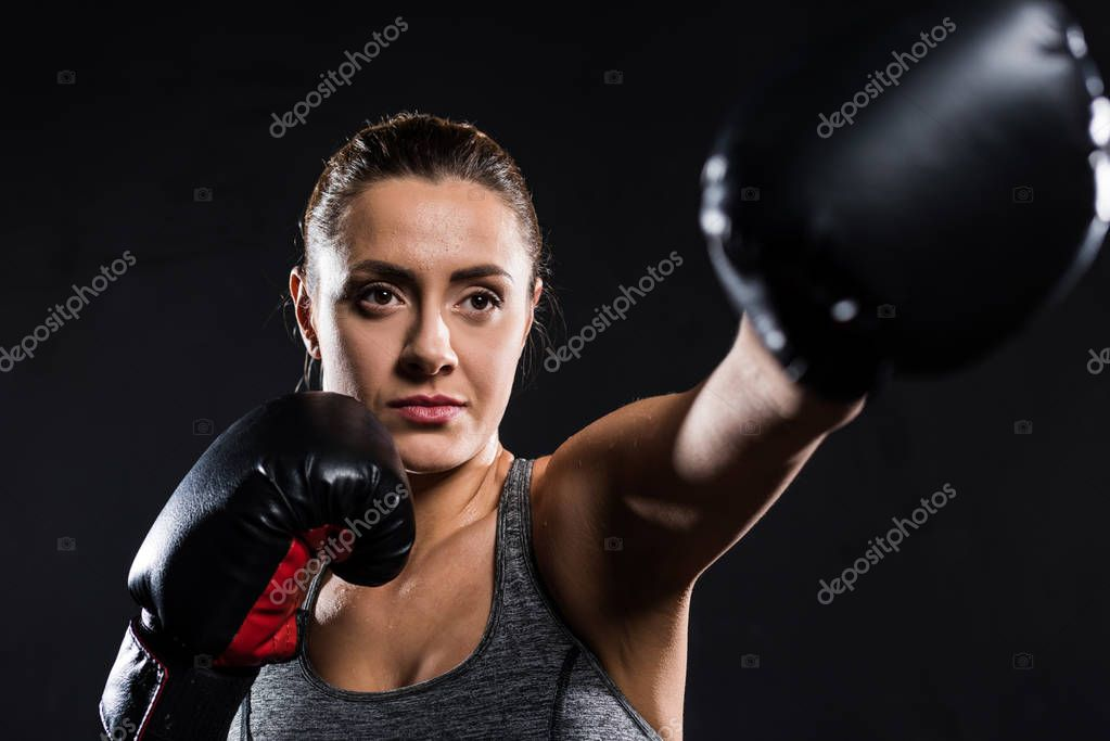 selective focus of young sportswoman boxing isolated on black