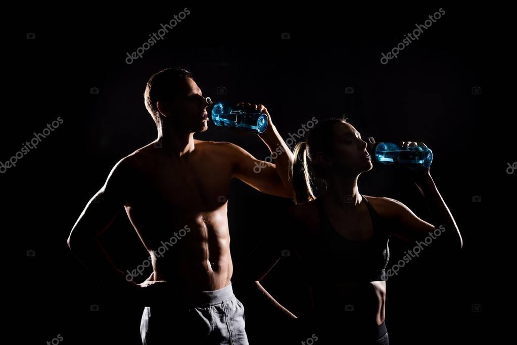 silhouettes of athletic young couple drinking from bottles isolated on black