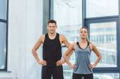 portrait of smiling man and woman akimbo standing in gym