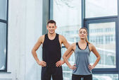 Photo portrait of smiling man and woman akimbo standing in gym