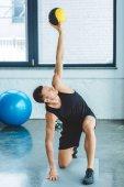 Fotografie konzentrierte sich junge Sportler trainieren mit Ball im Fitness-Studio