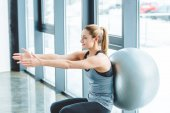 Photo smiling sportswoman exercising with fitness ball in gym