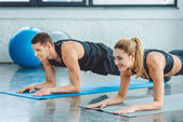 Photo couple doing abs exercises on mats before workout in gym