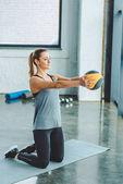 Fotografie Sportlerin, die Übungen mit Ball im Fitness-Studio