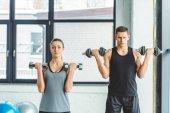 mladý muž a žena cvičení s činkami v posilovně