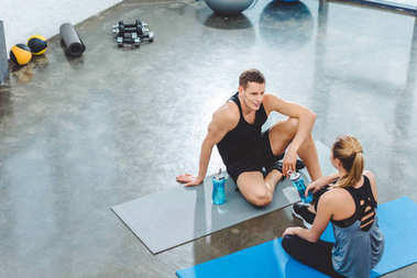 high angle view of sportsman and sportswoman with bottles of water sitting on yoga mats and looking at each other in gym