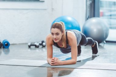 sporty young woman doing plank exercise on yoga mat