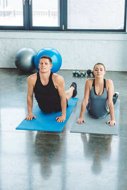 couple stretching on mats together in gym