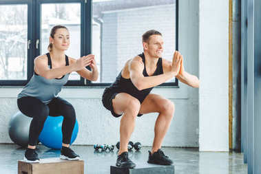 man and woman having cross training in gym